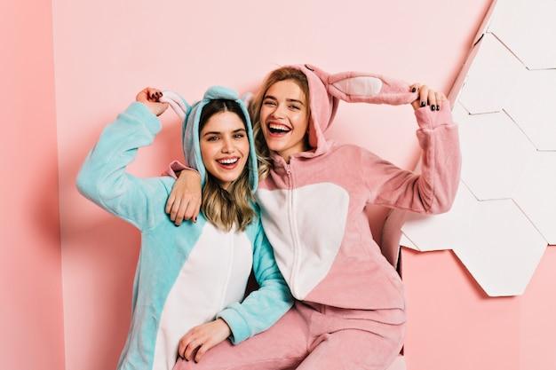 Hermanas alegres en kigurumi de pie en la pared rosa