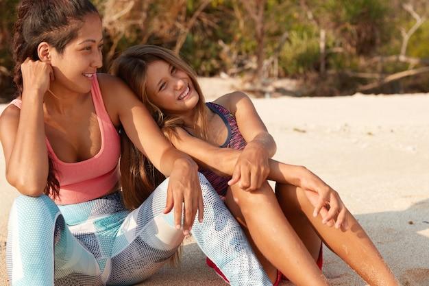 Hermanas alegres pasan tiempo de recreación en la playa, usan ropa deportiva