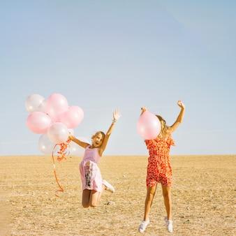 Hermanas alegres saltando con globos