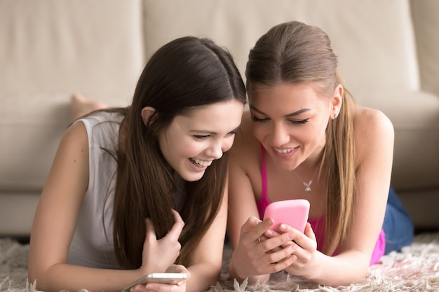 Hermanas compartiendo fotos divertidas en celular