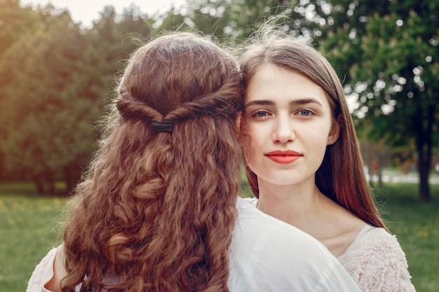 Hermanas elegantes y con estilo en un parque de primavera