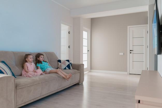 Hermanas encantadoras viendo televisión en casa