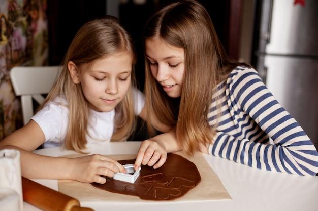 Hermanas felices en la cocina de la casa en la mesa recortan galletas con forma de corazón de la masa