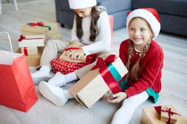 Hermanas felices desenvolver regalos o regalos de navidad