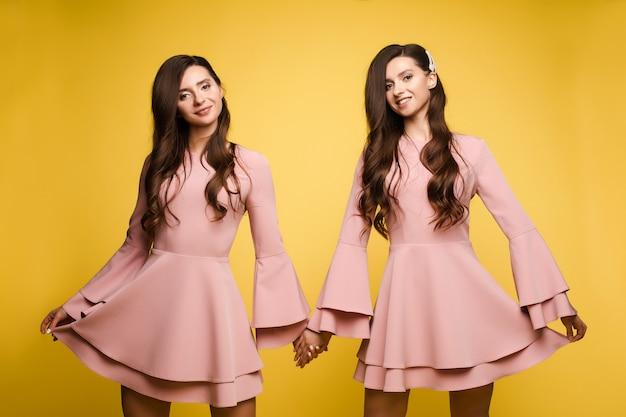 Hermanas felices en vestidos de color rosa sonriendo y de pie juntos.