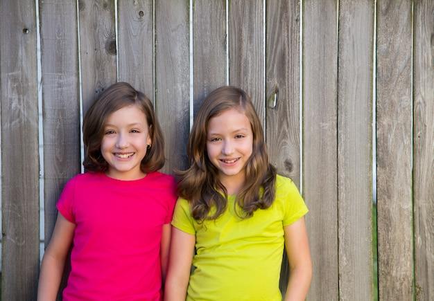 Hermanas gemelas con diferente peinado posando en la cerca de madera