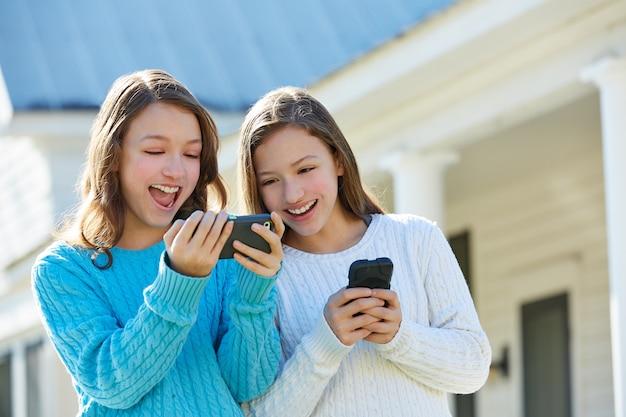 Hermanas gemelas divirtiéndose con tecnología smartphone.