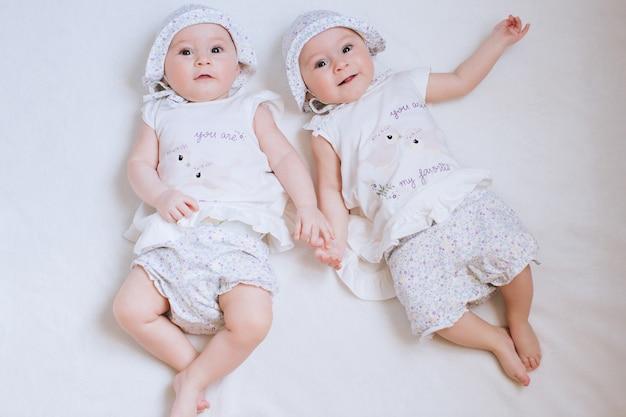 Hermanas gemelas felices en casa en la cama