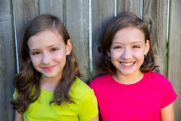 Hermanas gemelas felices que sonríen en la cerca de madera del patio trasero