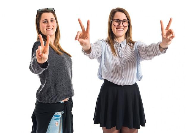 Hermanas gemelas haciendo gesto de victoria