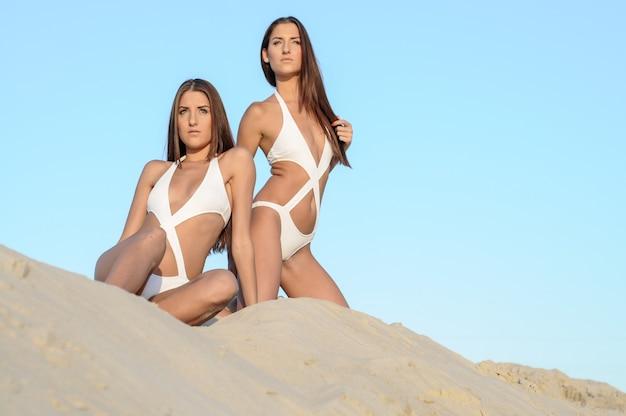 Hermanas gemelas hermosas felices divirtiéndose juntos, vistiendo trajes de baño de moda, sonriendo, posando en la playa