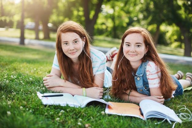 Hermanas gemelas jengibre idénticas que estudian en un parque de la ciudad. pasar un buen rato en la universidad o en la escuela, listos para protegerse el uno al otro del acoso. concepto de amistad y apoyo.