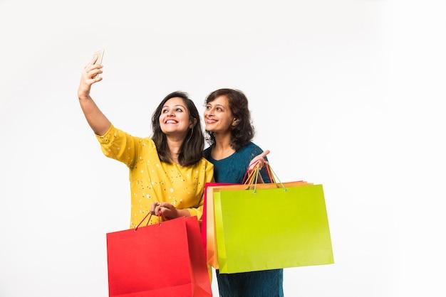 Hermanas indias madre hija de compras con bolsas de colores, comprobar el teléfono inteligente o tomar selfie mientras está de pie aislado sobre fondo blanco.