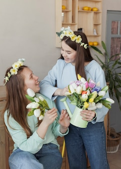 Hermanas jóvenes sosteniendo flores y mirándose