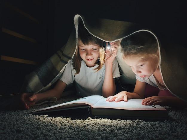 Hermanas leyendo un libro por la noche.