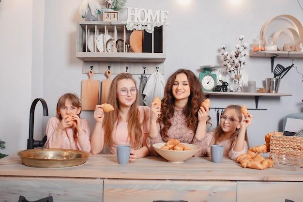 Hermanas lindas de pie en una cocina y come bollos