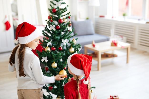 Hermanas niñas mirando el árbol de navidad, salón interior