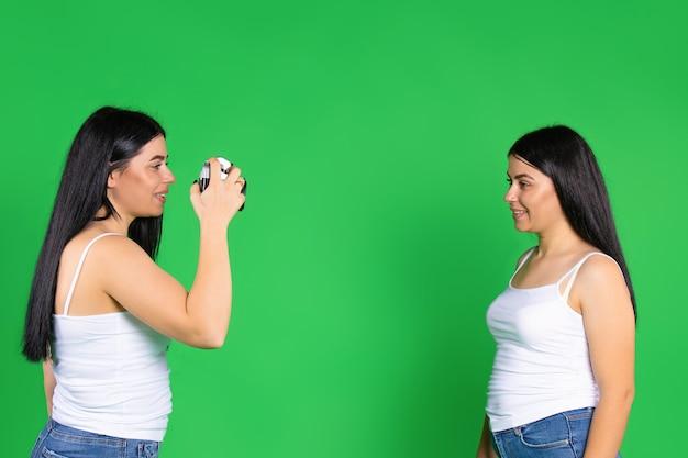 Las hermanas posan y toman fotografías con una cámara vintage fondo verde aislado