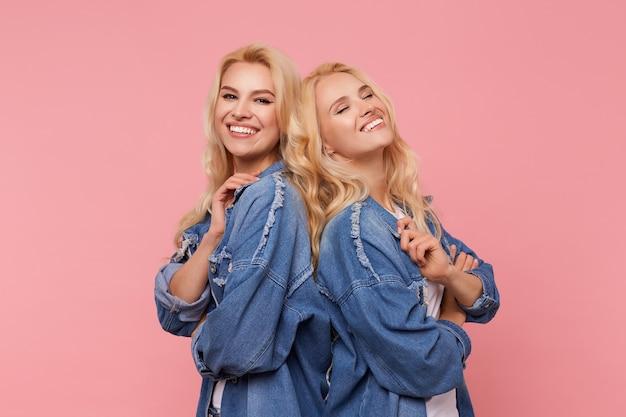 Hermanas rubias de pelo largo atractivas jovenes alegres que miran con gusto a la cámara con sonrisas encantadoras mientras están de pie espalda con espalda contra el fondo rosa
