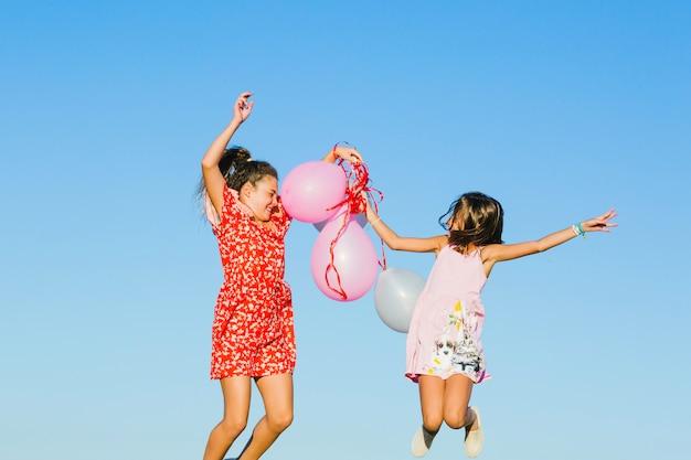 Hermanas saltando con globos