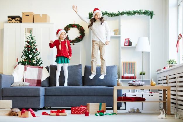 Hermanas saltando y jugando en el sofá, niñas con gorro de papá noel