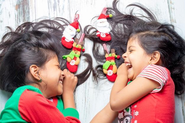 Hermanas sonrientes decorando su cabello con adornos navideños