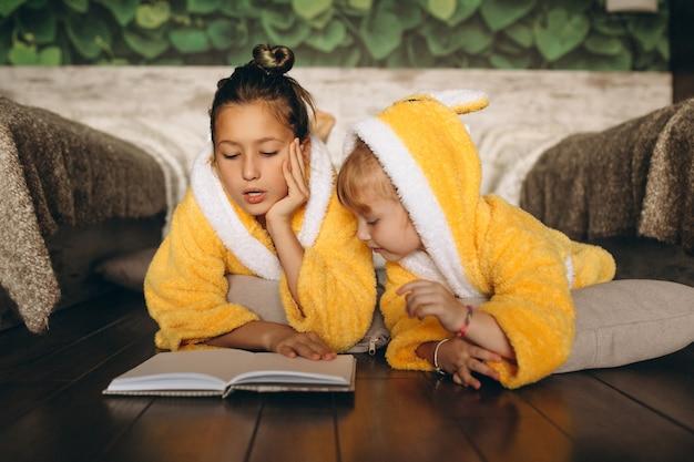Hermanas tumbadas en el suelo y leyendo el libro.