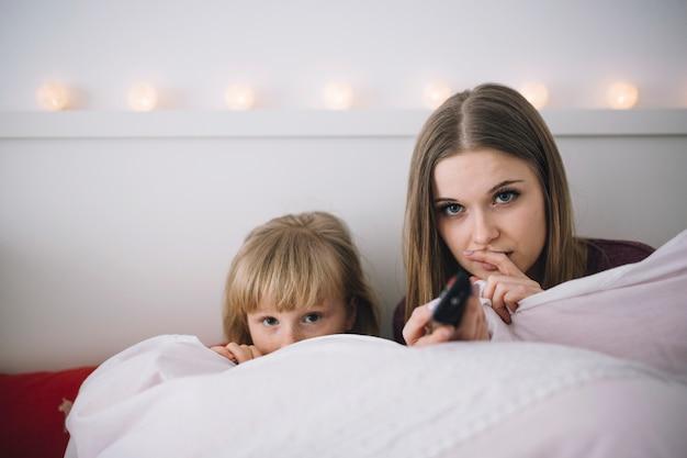 Hermanas viendo la televisión en la cama