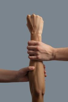 Hermandad de la humanidad. primer plano de dos manos de piel clara sosteniendo la muñeca y el antebrazo de la mano de piel oscura