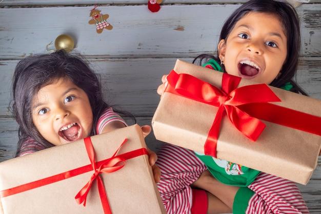 Hermanitas abriendo sus regalos el día de navidad