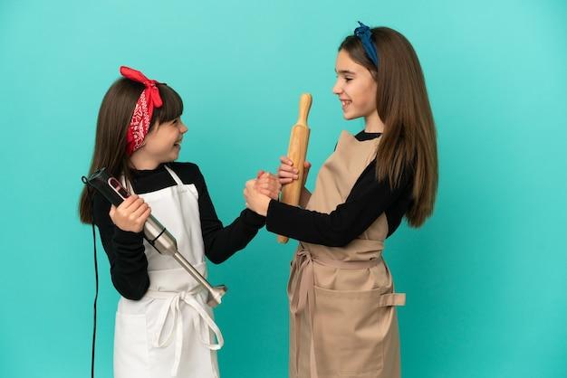Hermanitas cocinando en casa aislado sobre fondo azul apretón de manos después de un buen trato