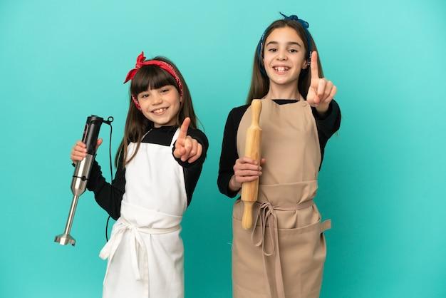 Hermanitas cocinando en casa aislado sobre fondo azul mostrando y levantando un dedo