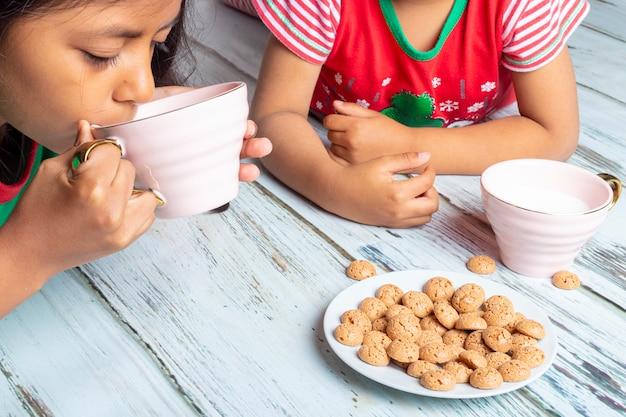 Hermanitas comiendo galletas con leche el día de navidad