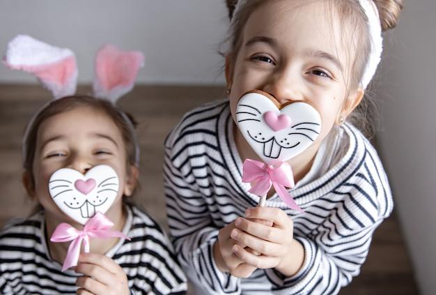 Hermanitas divertidas con panes de jengibre de pascua en forma de caras de conejito y con orejas de conejo.
