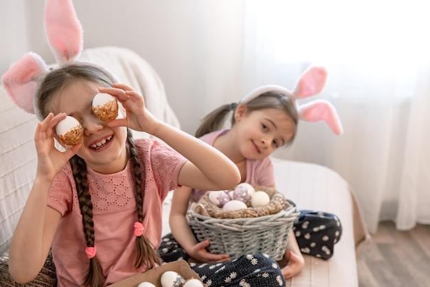 Hermanitas con orejas de conejo, con huevos de pascua en casa en el sofá