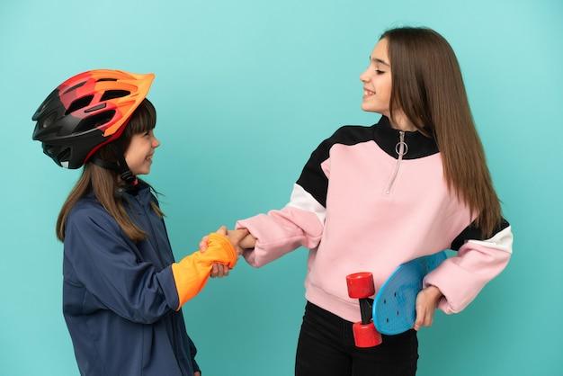 Hermanitas practicando ciclismo y patinador aislado sobre fondo azul apretón de manos después de un buen trato