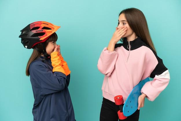 Hermanitas practicando ciclismo y patinador aislado sobre fondo azul cubriendo la boca con las manos por decir algo inapropiado