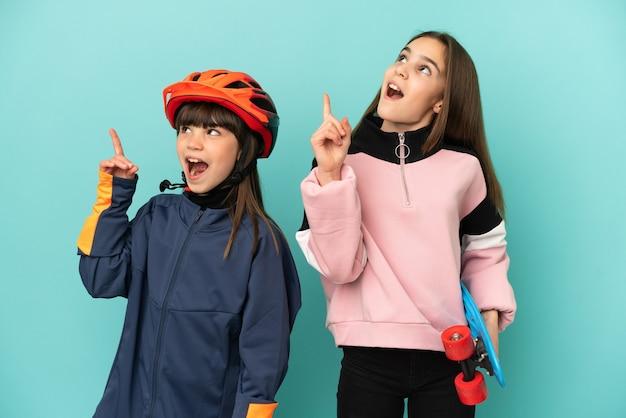 Hermanitas practicando ciclismo y patinador aislado sobre fondo azul pensando en una idea apuntando con el dedo hacia arriba
