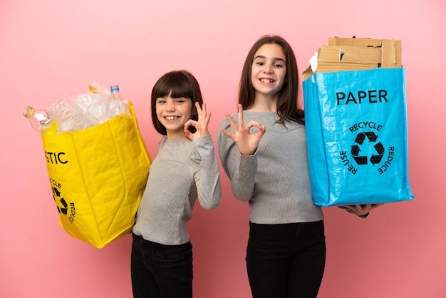 Hermanitas reciclando papel y plástico aislado sobre fondo rosa mostrando un signo de ok con los dedos
