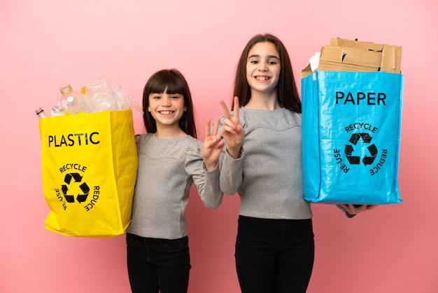 Hermanitas reciclando papel y plástico aislado sonriendo y mostrando el signo de la victoria