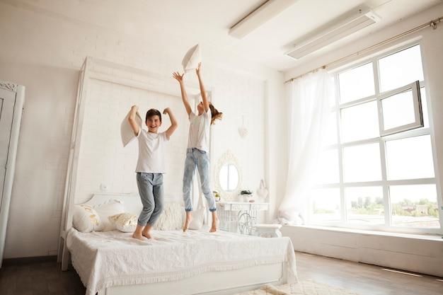 Hermanito y hermana divirtiéndose mientras saltan en la cama en el dormitorio