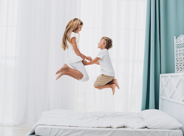 Hermanitos saltando juntos en la cama