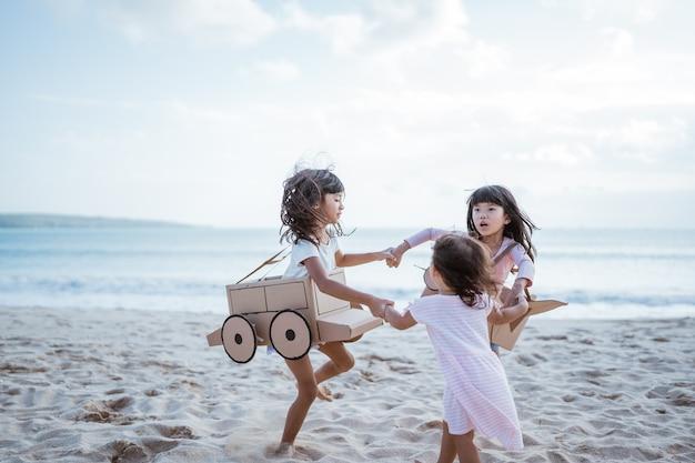Hermano y amiga jugando con avión de cartón y coche en la playa