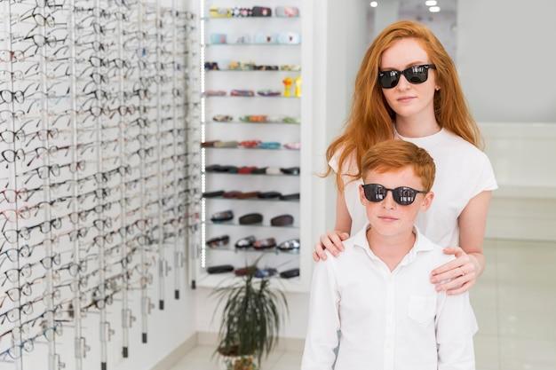 Hermano y hermana con anteojos negros parados juntos en la tienda de óptica