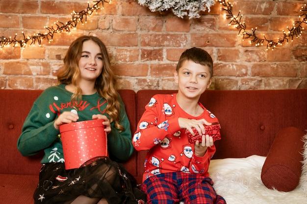 Hermano y hermana en casa en el sofá feliz abriendo regalos de año nuevo