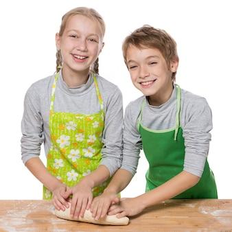 Hermano y hermana, despliegue de pasteles para hornear en una mesa de cocina sobre fondo blanco.