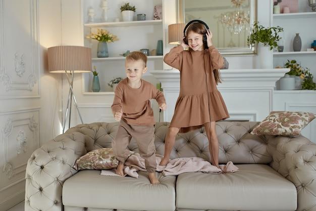 Hermano y hermana se divierten en casa y saltan en el sofá
