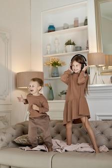 Hermano y hermana se divierten en casa y se suben al sofá. los niños bailan y escuchan música con auriculares.