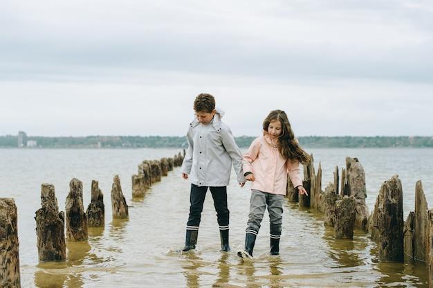 Hermano y hermana se divierten y juegan cerca del mar.