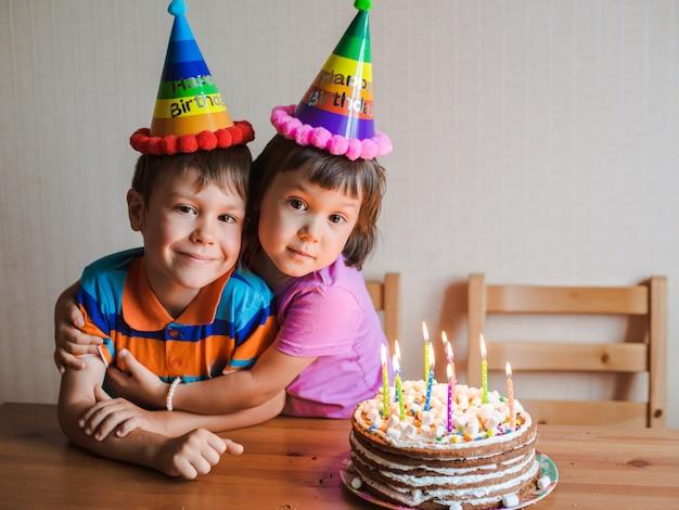 Hermano y hermana están comiendo un pastel de cumpleaños y abrazando.